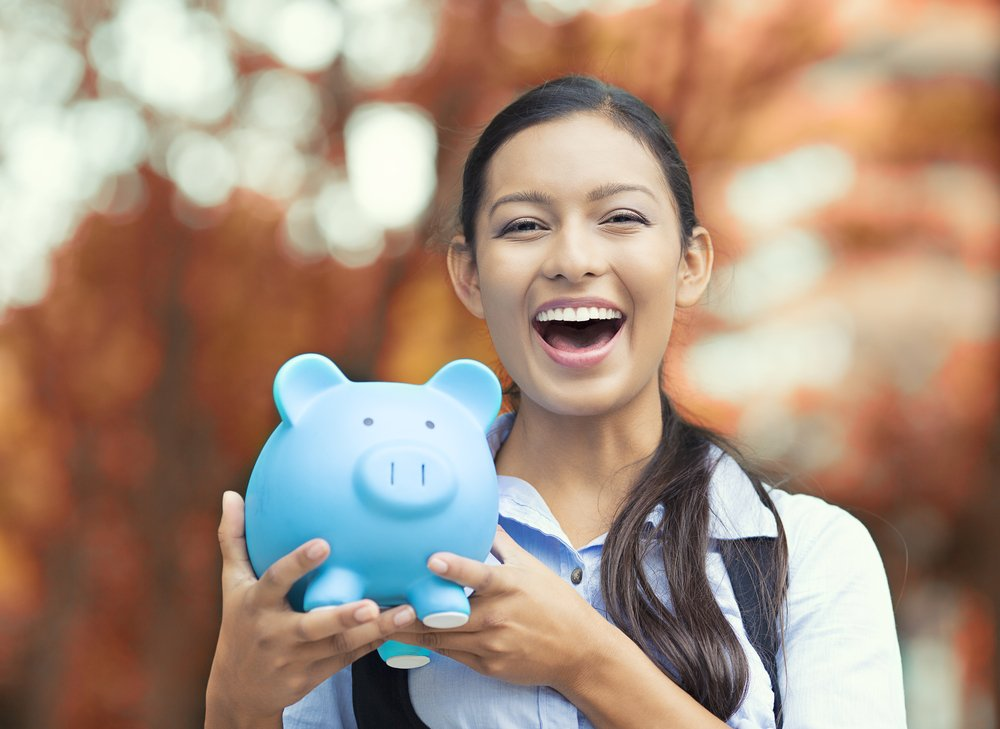 Closeup portrait happy, smiling business woman, bank employee holding piggy bank, isolated outdoors indian autumn background. Financial savings, banking concept. Positive emotions, face expressions